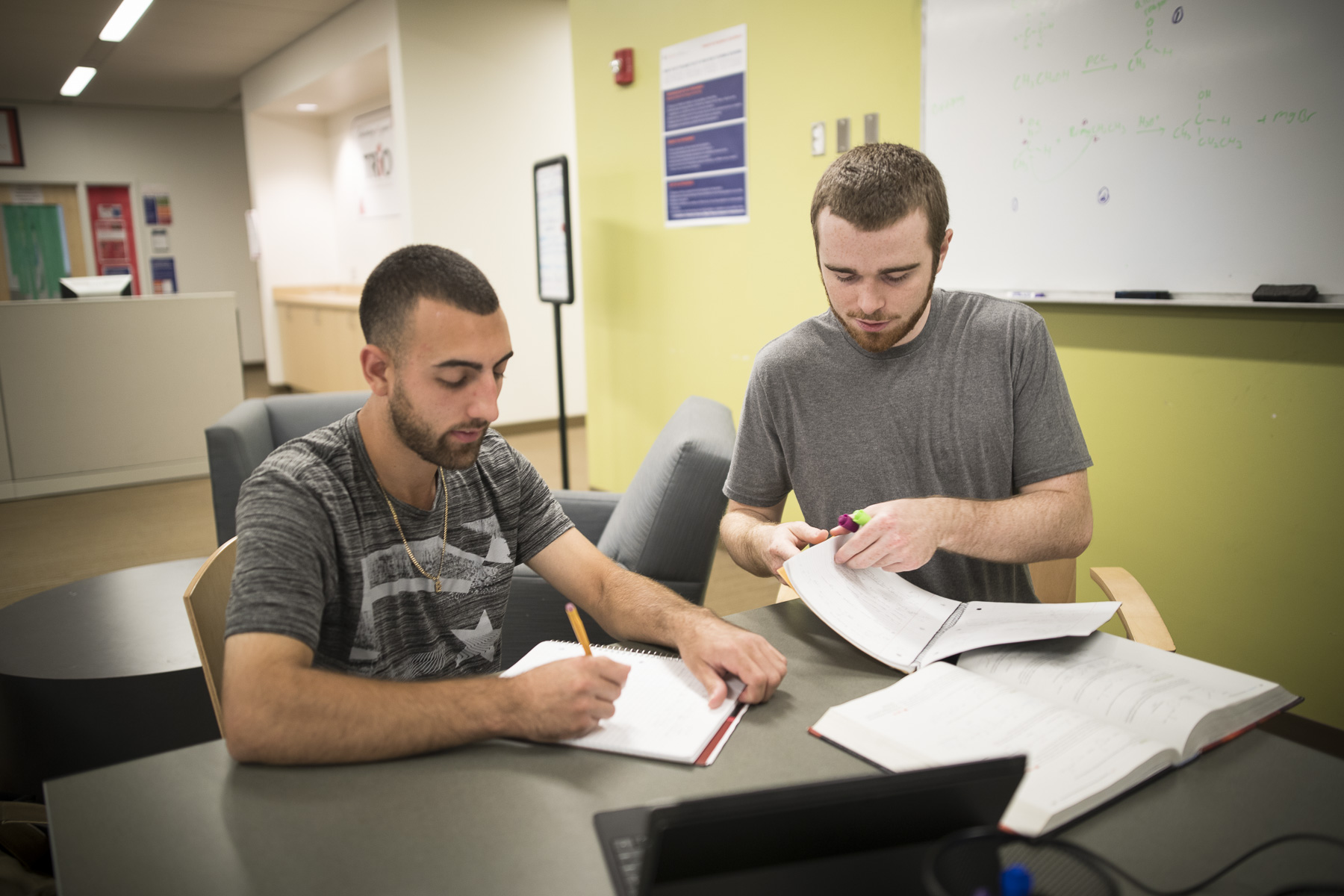 Two male students sit together in the library to study for a paper.