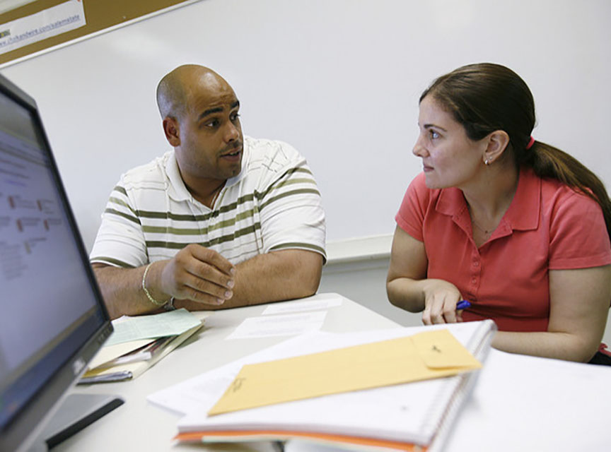 Faculty member and student working together in front of a computer