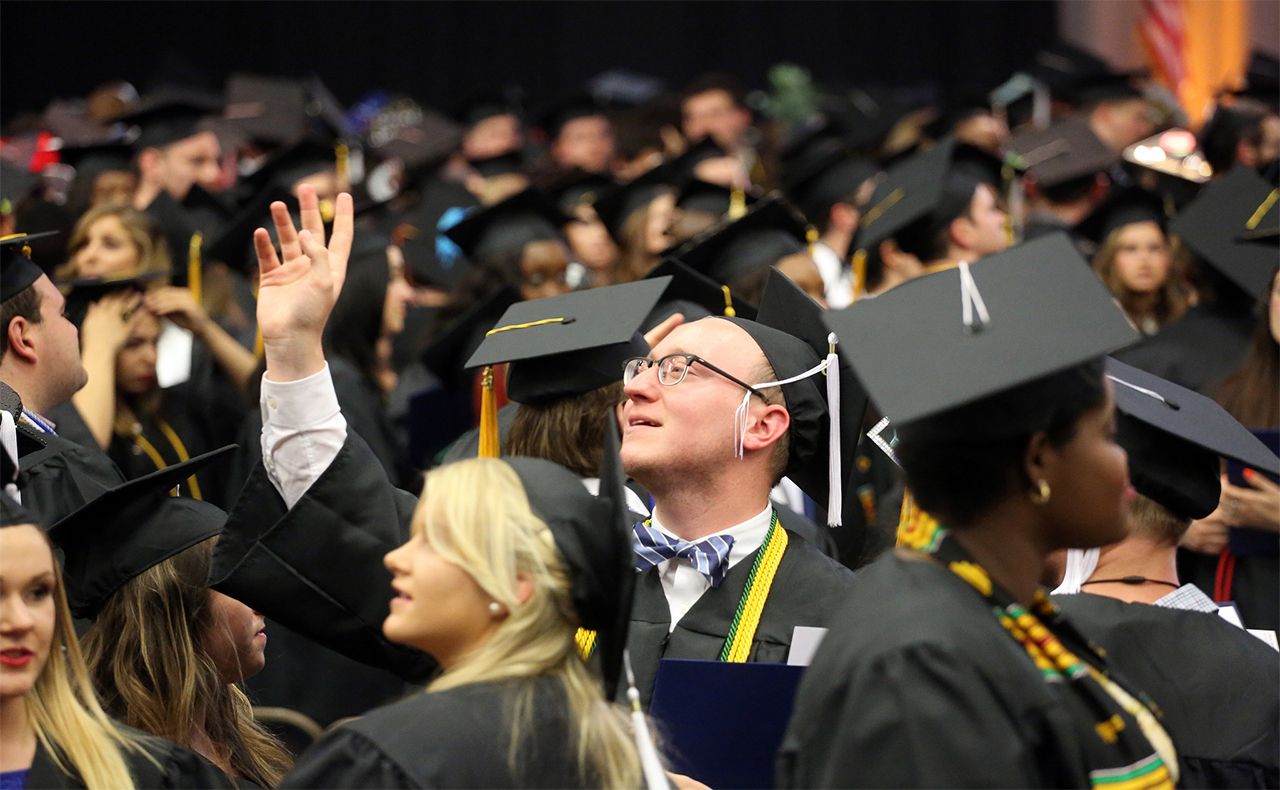 Student waiving at commencement