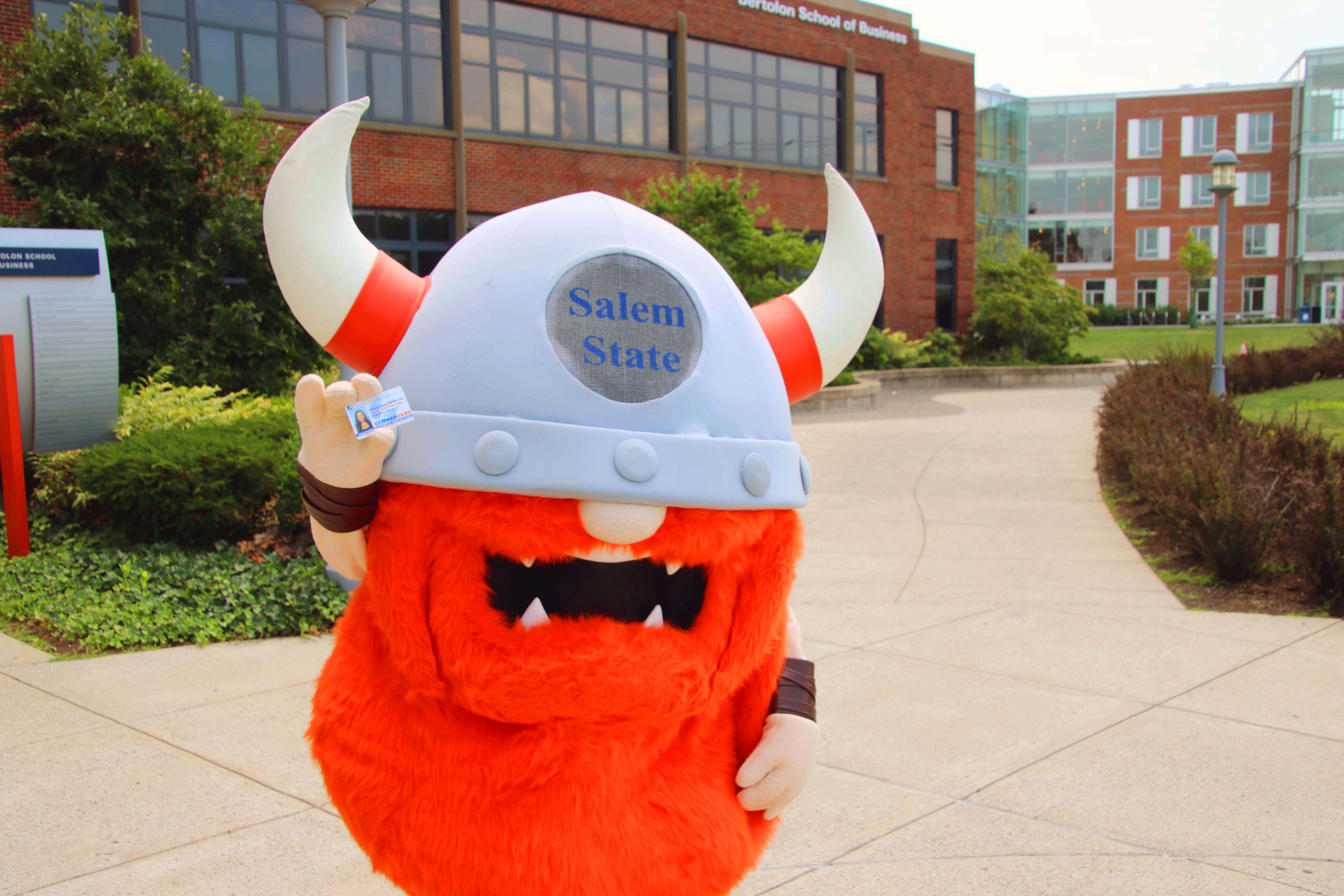 Superfan stands in front of the Bertolon School of Business holding a ClipperCard.