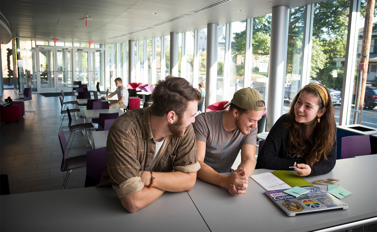 three students study together at a table in the Sophia Gordon Center.