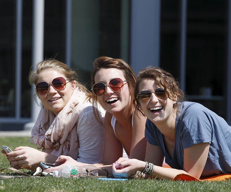 Three female students enjoy the summer weather in Salem State's North Quad
