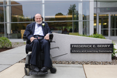 Frederick Berry in wheelchair outside of new library building, positioned in front of sign titled Frederick E. Berry Library and Learning Commons