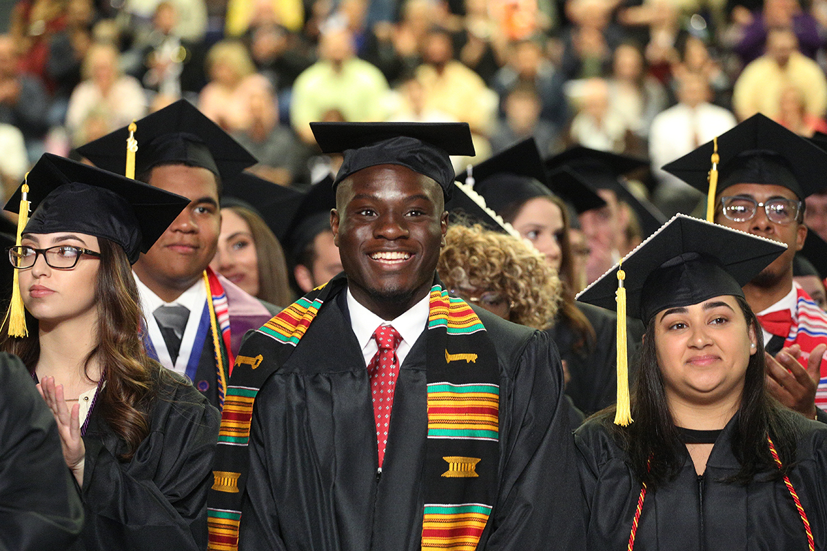 e47ec22a853 A graduate standing with his classmates in Rockett Arena at Commencement