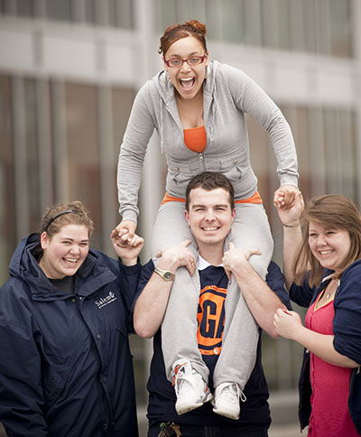 Four students gather outside of Marsh Hall with one student sitting on another's shoulders