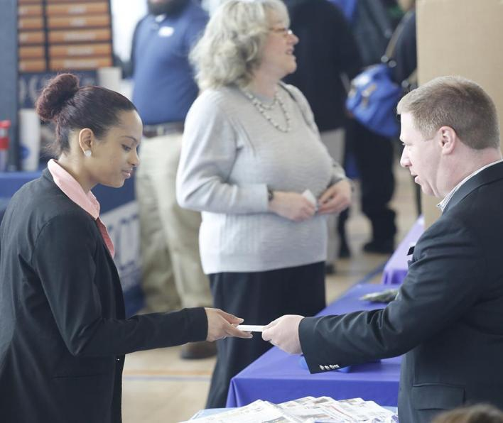 An employers hands a student his business card.