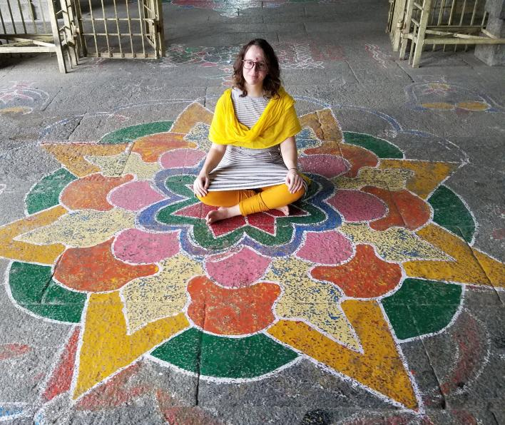 Emily Whipple sitting on mandala pattern painted on stone