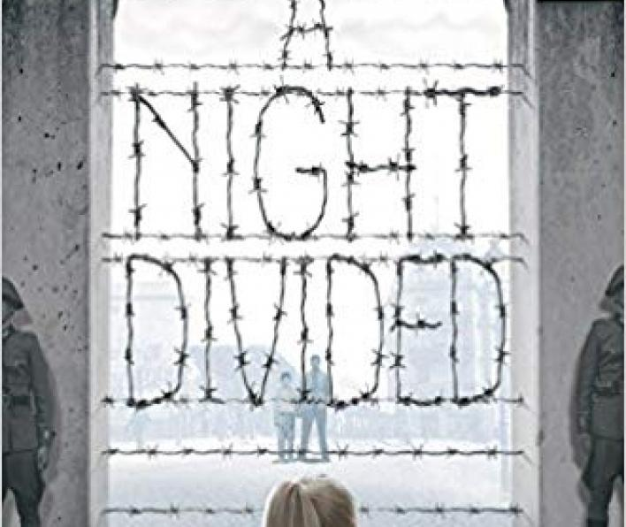 Image of book cover with large broken lines spelling out the title a night divided. A girl with her back to the viewer looks at the words.