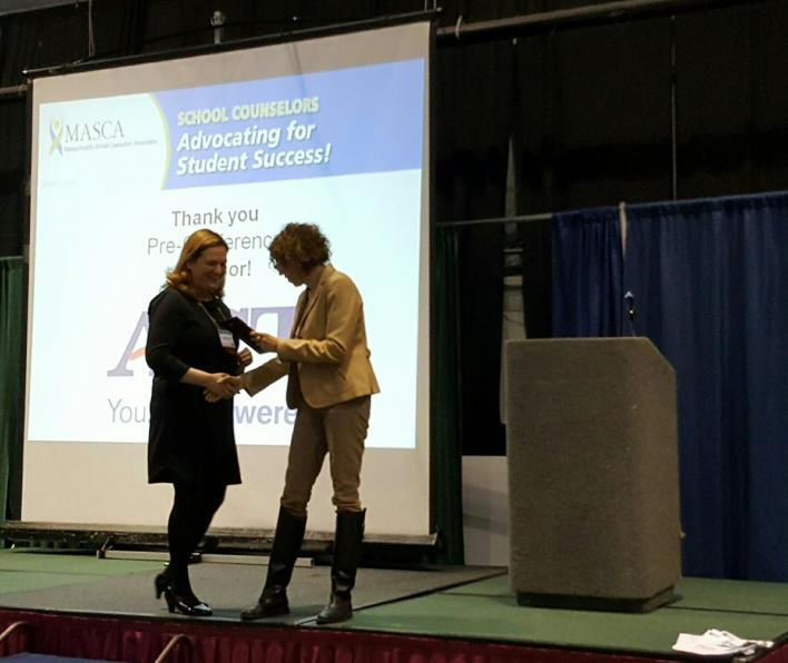 Dr. Laurie Dickstein-Fisher shaking hands with a presenter on stage as she receives her School Counselor of the Year award. An illegible slide is projected in the background. Dr. Dickstein-Fisher and the presenter are standing in front of a podium.