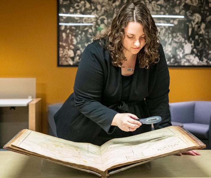Jen Ratliff, 2018 graduate at Salem State, uses a magnifying glass to look at a historical map of Salem in the Salem State Archives.