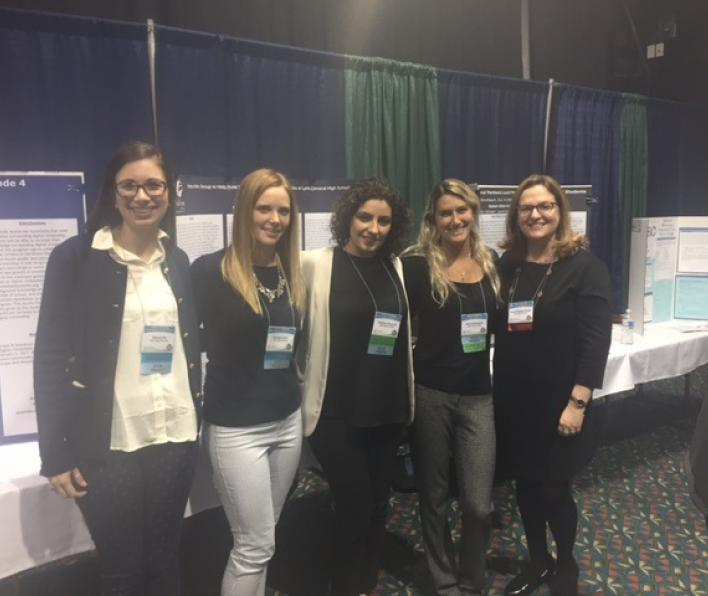 Four graduate students pose with Dr. Dickstein-Fischer in front of their poster presentation at the 2017 MASCA conference