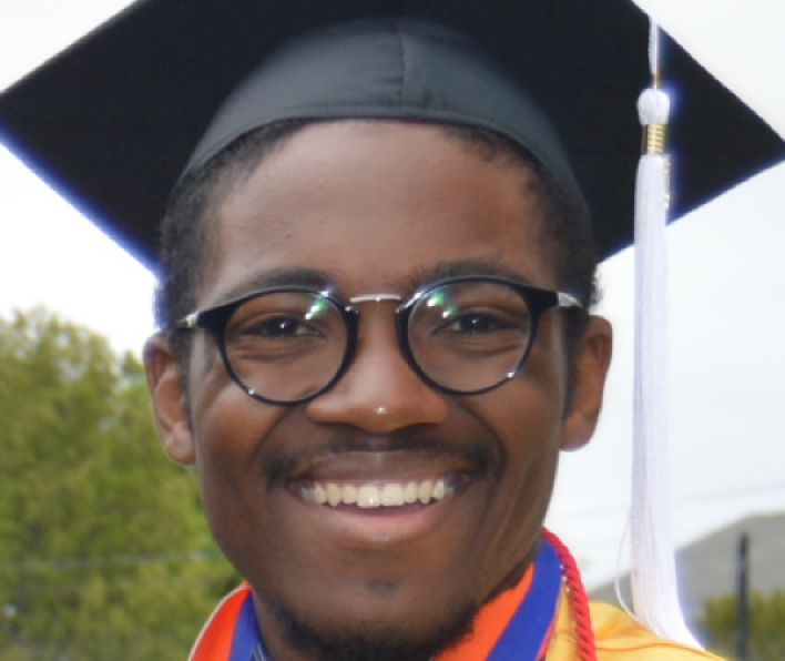 Jordan Hill wears his graduation cap and gown and smiles during the 2018 Salem State Commencement.