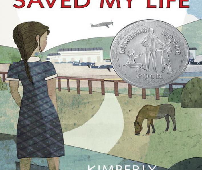 Cover image of the War That Saved My Life. A girl with brown hair in a long braid wearing a grey dress and black shoes looks over a field with a horse. Behind the horse is a fence that separates the field from an airfield with airplanes parked and one taking off in mid-air. There is a Newberry Honor Book seal on the cover above the horse.