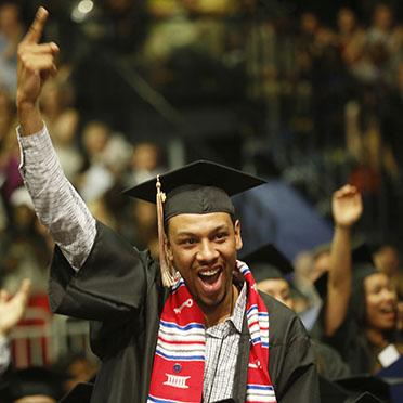 A graduating student at commencement 2016 is very happy to receive his diploma