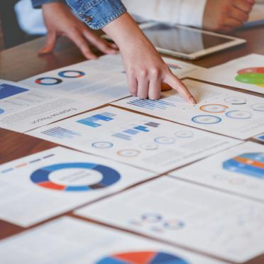 In this stock photo of research papers, fingers point to sheets of paper with data and graphs.