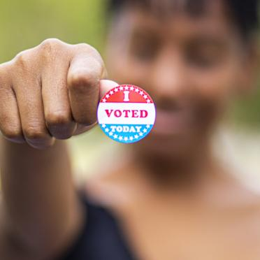 "A woman holds up her ""I Voted"" sticker"