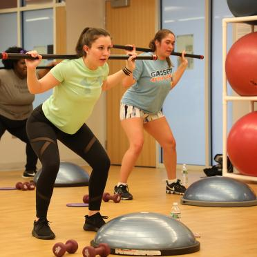 Three women lifting weights in the fitness studio