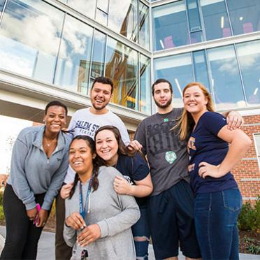 Six students pose in front of Viking Hall.