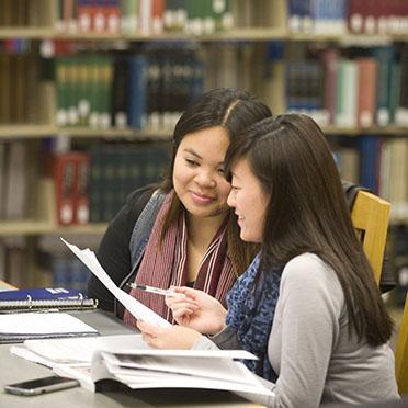 Two students study together in the library