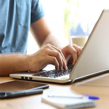 A male student types a paper on his laptop
