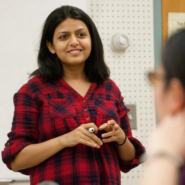 A female graduate school professor smiling at the front of the classroom