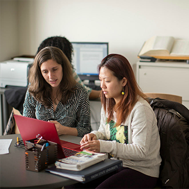 Two female students work together at the Writing Center