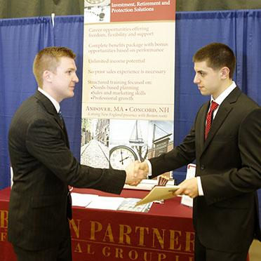 Career services career fair image featuring finance recruiter and male student