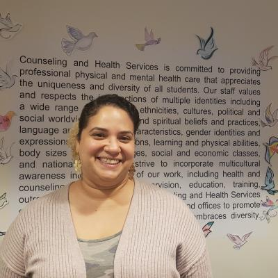 Administrative Assistant Melissa Muriel stands in front of a wall explaining Counseling and Health Services at Salem State.