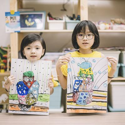 Two young children holding up their artwork
