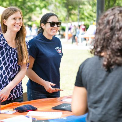 Two student leaders greet prospective members at the student organizations fair