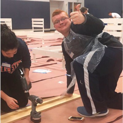 A student in the inclusive scholars program works on a volunteer building project.
