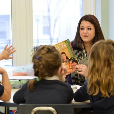 A female teacher facing a classroom of young students