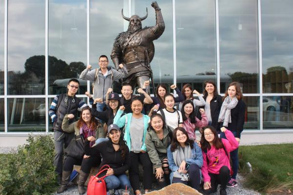International students pose in front of the Viking statue
