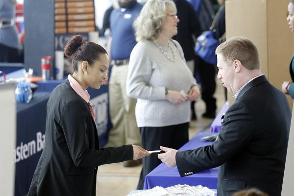 A job seeker and employer exchange business cards at the Salem State Career Fair.