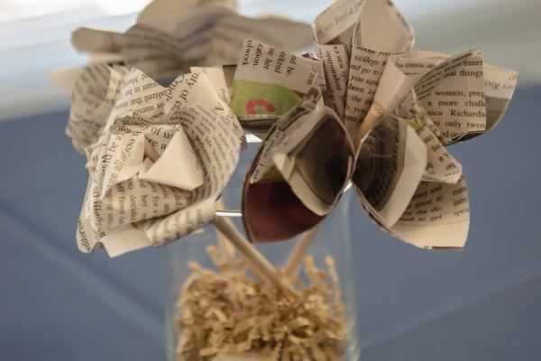 Flowers made out of newspapers in a vase.