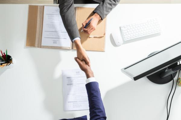 An overhead photo of two professionals shaking hands over a table.