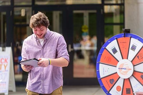 A student plays a game on his iPad in front of the Ellison Campus Center.