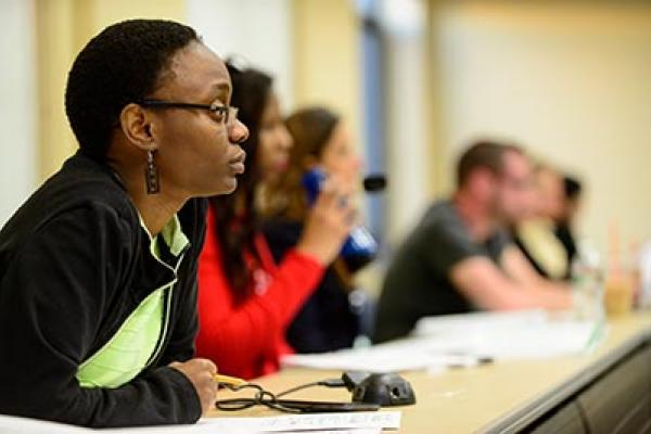 A student sits listening to her professor.