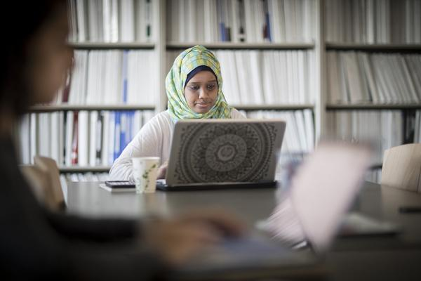 girl wearing headscarf, sitting at a large desk in front of a wall of bookshelves, using her laptop