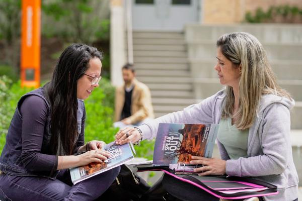 Two students talk outside at Salem State