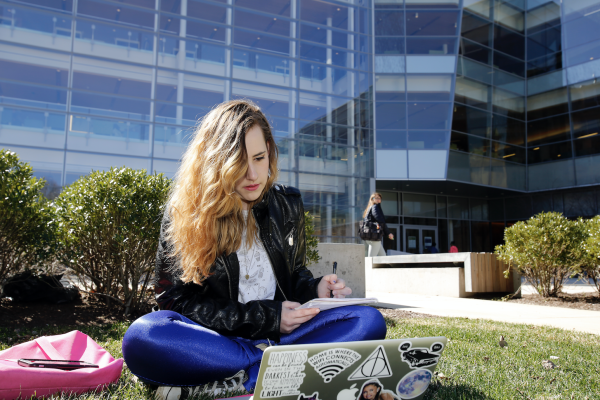 Girl sits in the quad with her laptop to register for tutoring.