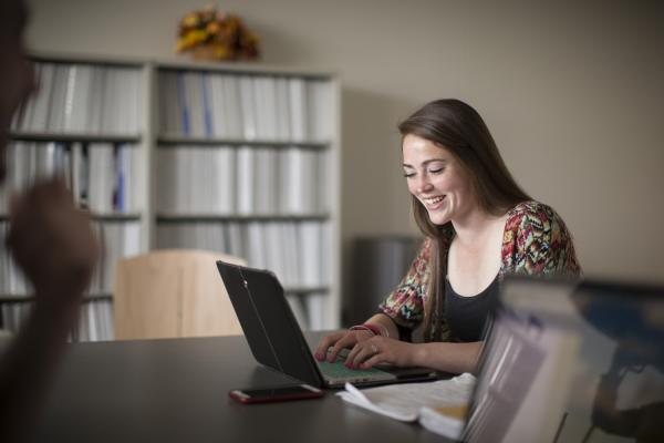 A young female student sits at a table and types at her laptop while smiling.