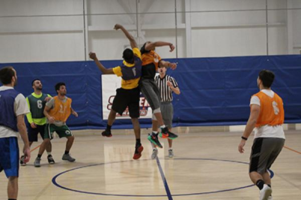 Opening tip, a group of male students playing basketball