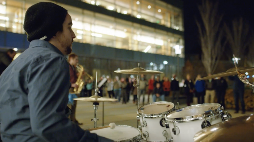 A student musician plays drums on the quad