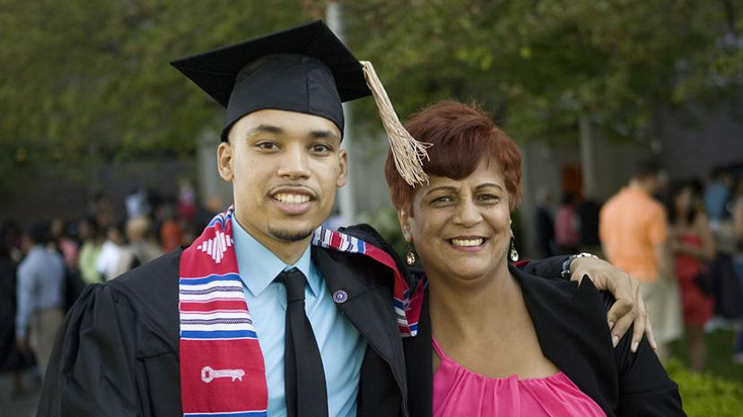 A new alum embraces his mother at his graduation