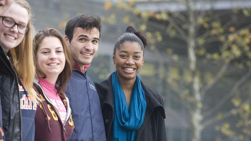 A group of students of diverse backgrounds enjoy a fall day on campus