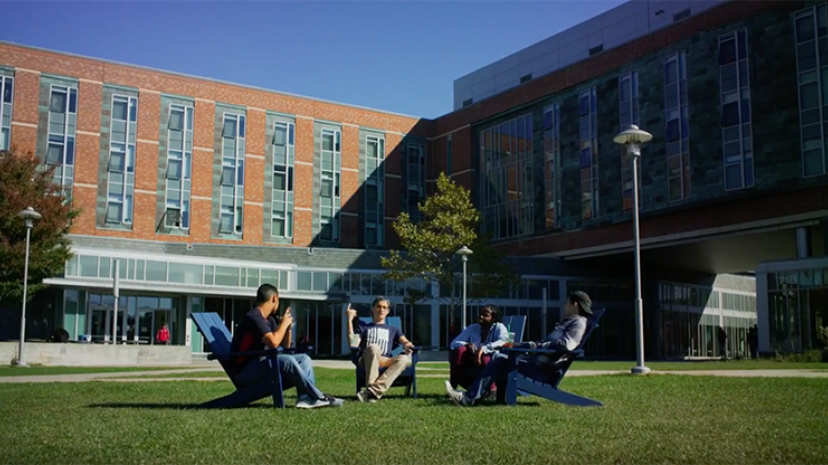Four students sitting in Adirondack chairs on the March quad