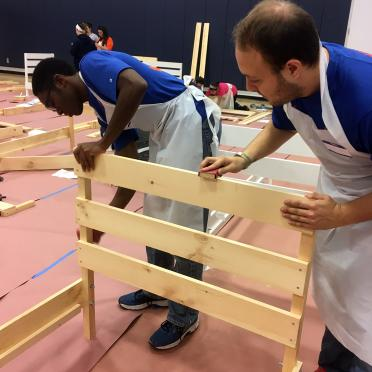 Two student volunteers construct a bed frame